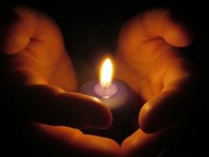 Zwei Hände, die eine Kerzenflamme umfassen, nur von dieser beleuchtet