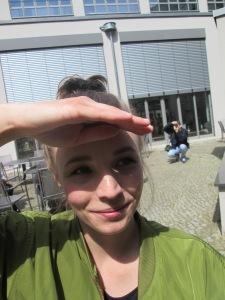 Porträt einer jungen Frau, die sich die Hand über die Augen hält, um gegen die Sonne zu sehen