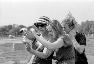 Zwei Studentinnen assistieren einer blinden Fotografin.