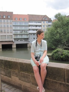 Nadine sitzt auf einer Mauer. Im Hintergrund ein Haus und Bäume.