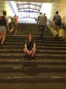 Junge Frau auf Bahnhofstreppe sitzend mit laufenden Menschen im Hintergrund.