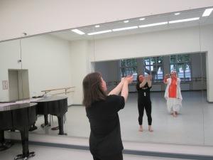 Eine Frau, die eine Tanzbewegung macht, vor einem Spiegel, in dem man auch die Fotografin dieses Bildes spiegelt.