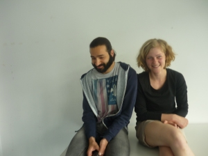 Eine junge Frau und ein junger Mann sitzen auf einem weißen Tisch vor einer weißen Wand.