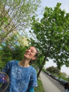 Eine lächelnde Frau vor Bäumen, vor ihr steigen Seifenblasen auf
