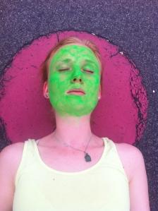 Das grün geschminkte Gesicht einer Frau vor einem rötlichen Hintergrund