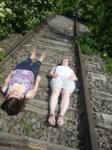 Zwei Frauen liegen auf den Schwellen zwischen zwei Gleisen