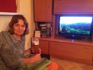 Barbara mit einem Fernseher im Hintergrund.