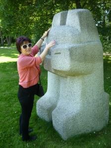 Eine Frau mit Sonnenbrille betastet eine Steinskulptur im Park