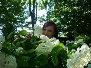Eine Frau, inmitten vieler grüner Büsche und Bäume
