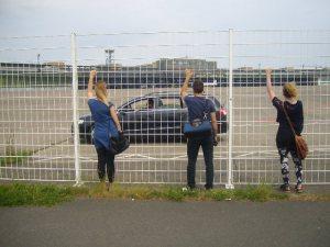 3 Menschen vor einem Zaun