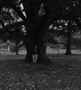 Person vor einem Baum aus größerer Entfernung aufgenommen
