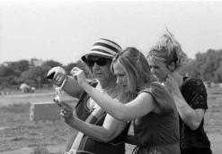 Eine Frau mit Sonnenbrille hält eine kleine Kamera. Zwei jüngere Frauen stehen dich hinter ihr und blicken konzentriert die Rückseite der Kamera.