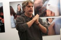 """Ein Mann mit grauen Haaren spricht vor den Bildern der """"Schönheit der Blinden"""". Er gestikuliert"""