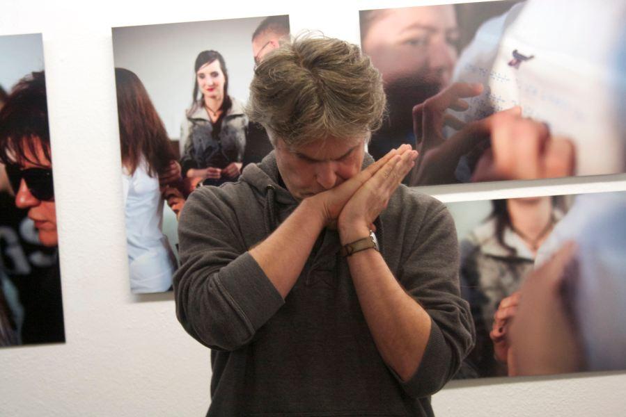 Der grauhaarige Mann scheint nachzudenken, das Gesicht auf die zusammengelegten Hände gelegt