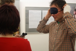 Ein Mann im karierten Hemd setzt sich eine Schlafbrille auf