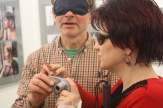 Ein Mann mit verbundenen Augen und die Frau mit Sonnenbrille hantieren gemeinsam an einr kleinen Kamera