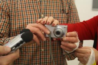 Ein kleiner Fotoapparat in den Händen eines Mannes, die eine Hand ist bandagiert. Die Hände einer Frau betasten die Kamera. Von links wird ein Mikrofon ins Bild gehalten