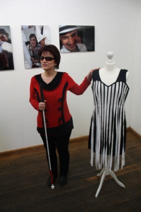 """Silja Korn im roten Pullover steht neben dem Kleid, das sie in der """"Schönheit der Blinden"""" trägt"""