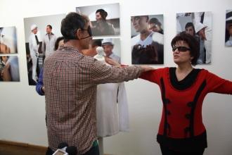 Ein Mann mit verbundenen Augen betastet die Frau im roten Pullover