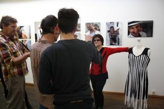 Workshopsezene. Die Frau im roten Pullover posiert. Im Vordergrund hantieren drei Männer.