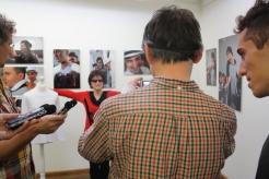 Ein Mann mit verbunden Augen fotografiert die Frau im roten Pullover.