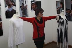 """Eine Frau im roten Pullover steht in der Ausstellung """"Die Schönheit der Blinden"""". Ihre ausgestreckten Arme berühren zwei Schneiderpuppen."""