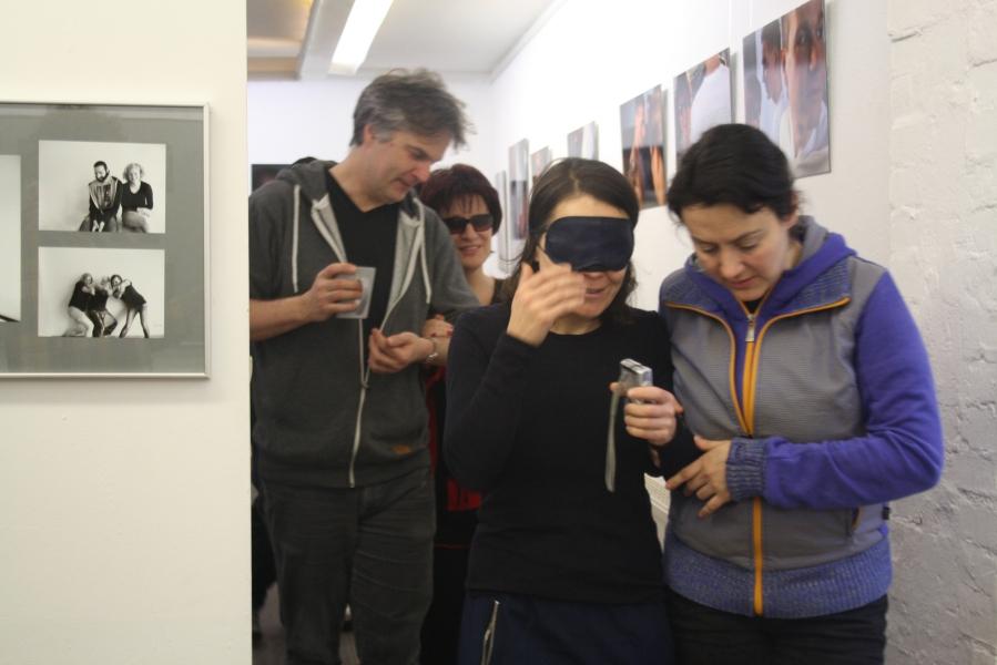 Eine Frau mit Augenbinde wird von einer jungen Frau am Arm geführt, dahinter wird eine Frau mit Sonnenbrille von einem Mann am Arm geführt.