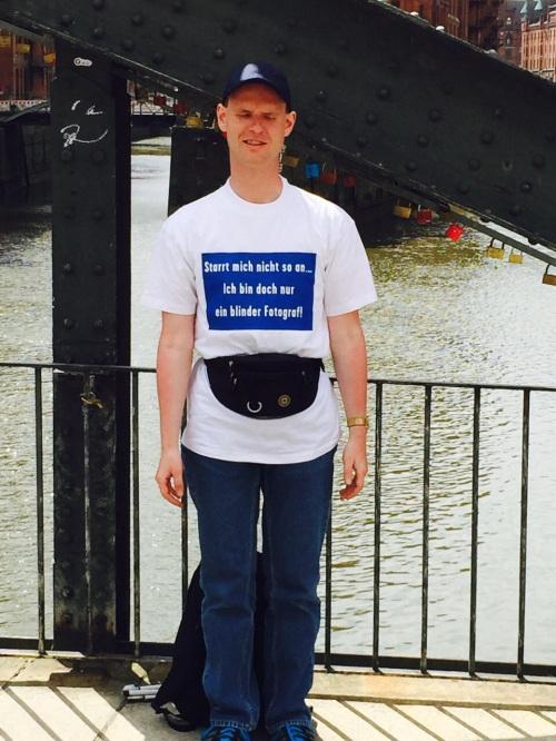 Christian mit einem T-Shirt auf dem steht: Starrt mich nicht so an ... Ich bin doch bloß ein blinder Fotograf.
