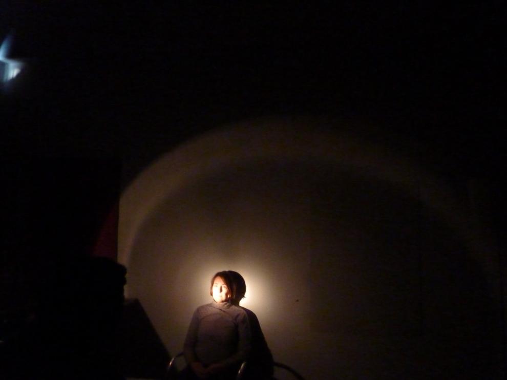 Schwarzer Hintergrund in dessen unterer Hälfte eine Person von einer Lichtquelle angestrahlt wird