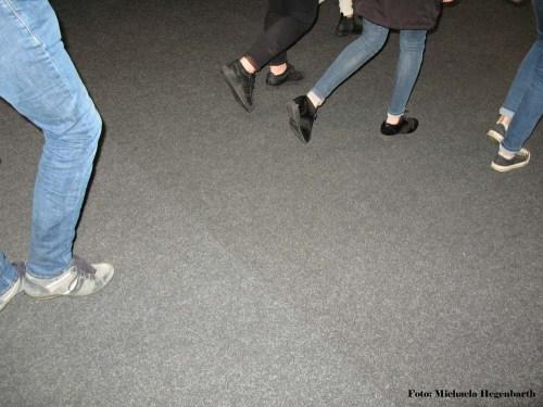 Füße und Hosenbeine in Bewegung auf Betonboden.