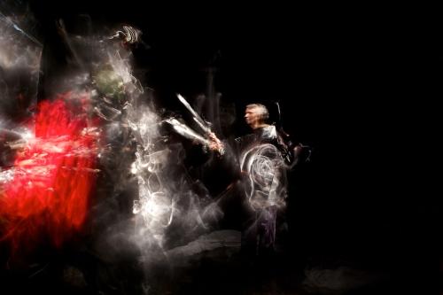 Eine geisterhaft beleuchtete Frau atakiert eine Lichtquelle mit einem Schwert.