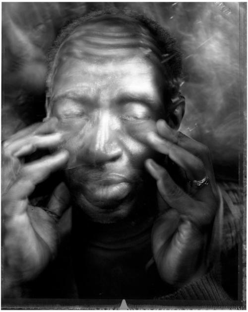 Ein Mann mit geschlossenen Augen betastet sein Gesicht