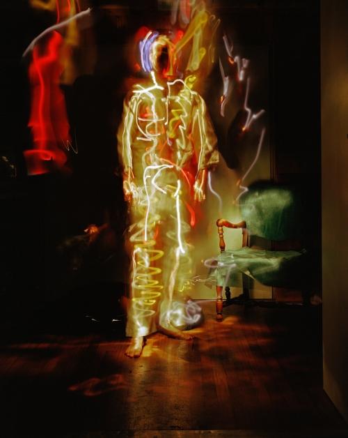 Ein grünlich beleuchteter Mann vor dunklem Hintergrund