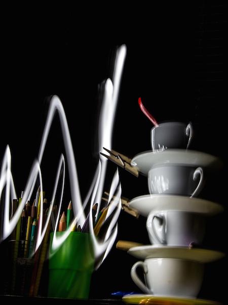 Gestapelte Tassen und aufrecht stehendes Besteck vor schwarzem Hintergrund